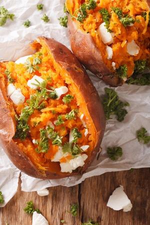 健康食品: 焼き芋を詰めたフェタチーズのチーズとパセリのクローズ アップ テーブルの上。上から垂直ビュー