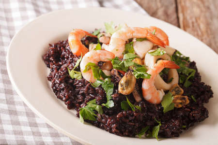 Paella from black rice with seafood close-up on a plate on the table. horizontal Stock Photo