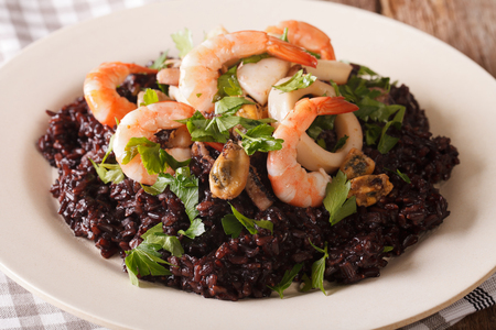 Risotto of black rice with seafood close up on a plate on the table. horizontal