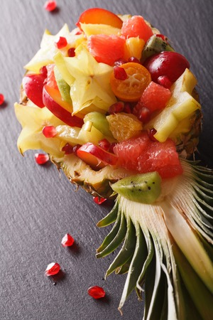 Ripe pineapple stuffed with fresh tropical fruits close-up on the table. vertical  Stock Photo