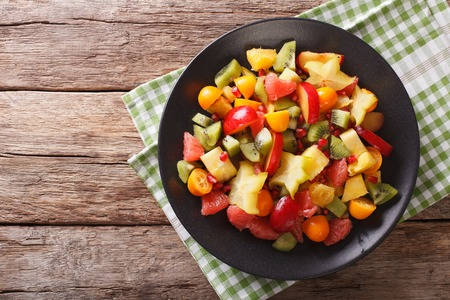 Fruit salad with orange, kumquat, pineapple, carambola, grapefruit, plum, pomegranate and kiwi close-up on a plate. horizontal view from above  Stock Photo