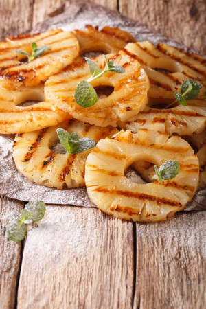 napkin ring: Homemade grilled pineapple on the paper on the table close-up. vertical  Stock Photo