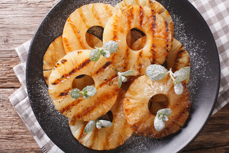 napkin ring: Delicious grilled pineapple with mint close up on a plate on the table. Horizontal view from above