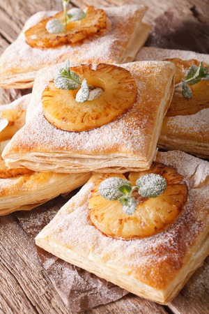 puff pastry pies with pineapple, decorated with mint close up on the table. vertical