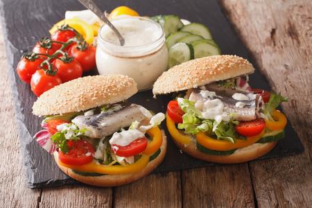 sandwich au hareng mariné, sauce et légumes frais sur un gros plan de table. horizontal