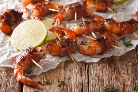 Grilled shrimp with bacon, thyme and lime close up on the table. Horizontal