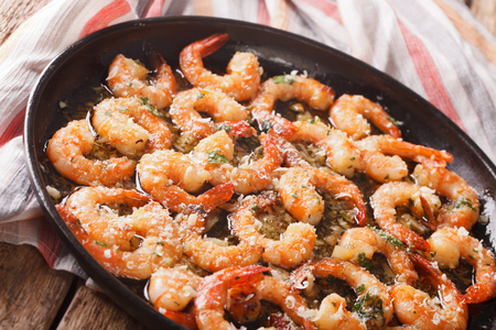 Fried shrimp in garlic sauce with parmesan cheese and herbs in a pan close-up. horizontal