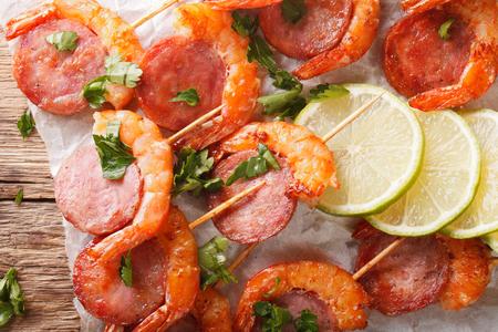 Delicioso camarón a la parrilla con chorizo ??en pinchos y hierbas closeup sobre la mesa. vista horizontal desde arriba