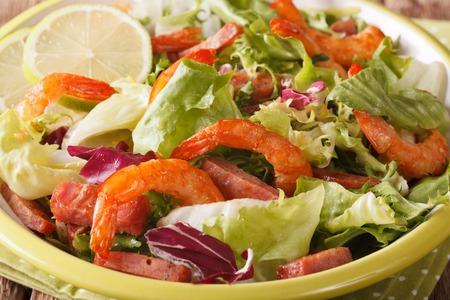 salad of fried shrimp with chorizo and mix lettuce macro on a plate. horizontal