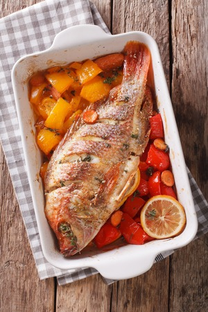 Tilapia fish baked with bell peppers, carrots and thyme close up in baking dish on the table. vertical view from above