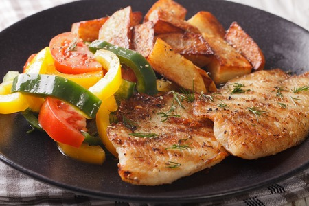 Grilled Tilapia fillet and potato wedges, fresh salad on a plate close-up. horizontal  Stock Photo