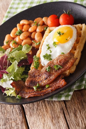 Delicious breakfast: fried egg, waffles, bacon, beans and salad close-up on a plate. Vertical  Stock Photo