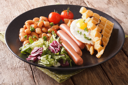Fried waffles with egg, sausages, beans and fresh salad close-up on a plate. horizontal
