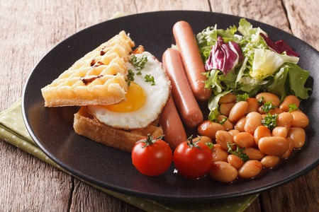 Healthy breakfast: waffle sandwich with egg, sausages, beans and salad close-up on a plate. horizontal  Stock Photo