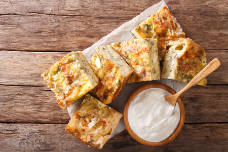 Traditional Serbian Gibanica with cheese, eggs and greens close-up on the table and yogurt. horizontal view from above Stock Photo