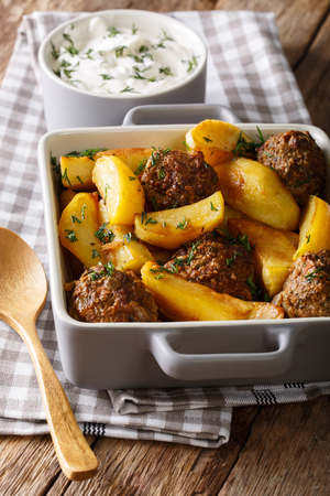 cooked pepper ball: Potato wedges and meatballs, herbs in a dish close-up on the table. vertical