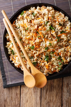 Thai spicy rice with minced meat and vegetables close-up on the table. vertical view from above Stock Photo