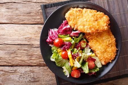 Chicken steak in breading Panko and fresh salad close-up on the table. horizontal view from above