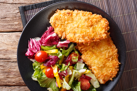 Chicken steak in breadcrumbs Panko and fresh vegetable salad close-up on the table. horizontal view from above