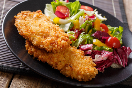 Chicken cutlet in a breaded and fresh mix of salad close-up on a table. horizontal