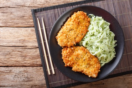 Japanese cuisine: chicken cutlets in breadcrumbs Panko and noodles with green tea Macha on the table. horizontal view from above