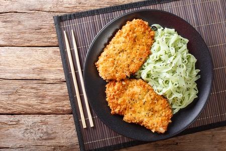 Japanse keuken: kipfilet in broodkruimels Panko en noedels met groene thee Macha op tafel. horizontale weergave van bovenaf Stockfoto