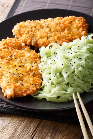 Asian food: steak in breaded Panko and green noodles with sesame close-up on the table. Vertical