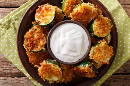 Delicious slices of zucchini in breadcrumbs with sour cream close-up on the table. horizontal view from above