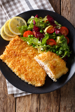 arctic ocean: Fish fillet of Arctic char in breadcrumbs and fresh salad on a plate close-up. Vertical view from above