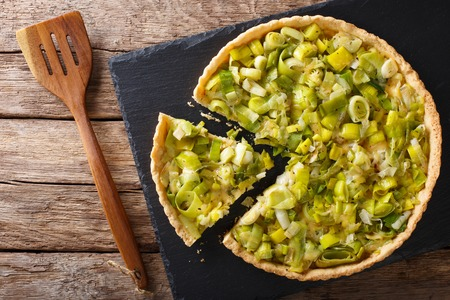 Sliced tart with leek and cheese close-up on the table. Horizontal view from above Reklamní fotografie - 75483732