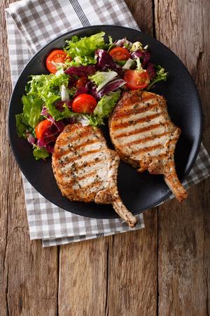 Würziges Schweinefleischkotelett BBQ mit gemischtem Salat auf einer Plattennahaufnahme auf dem Tisch. Vertikale Ansicht von oben Standard-Bild - 75488492