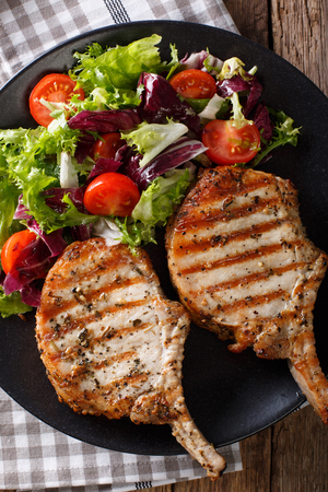 Grilled pork steak with bone, fresh vegetable salad close-up on plate. Vertical view from above