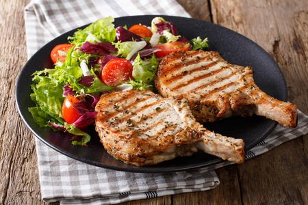 Grilled pork steak with bone, fresh vegetable salad close-up on plate. Horizontal