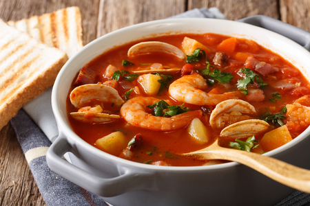 Homemade tomato clam chowder soup close-up in a saucepan on a table. horizontal Stock Photo