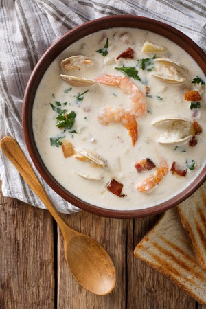 American food: New England clam chowder soup close-up on a in a bowl on the table. Vertical view from above Stock Photo