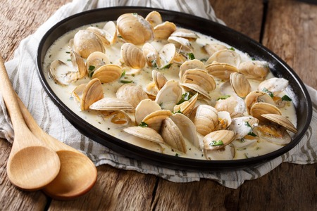 ridged: Delicious clams in a creamy sauce with parsley closeup on a plate on a table. horizontal