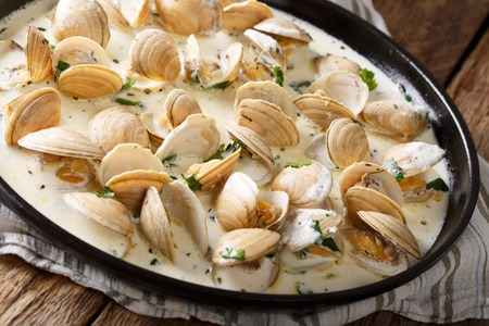 ridged: Stewed clam in a creamy sauce with herbs and garlic close-up on a plate. horizontal
