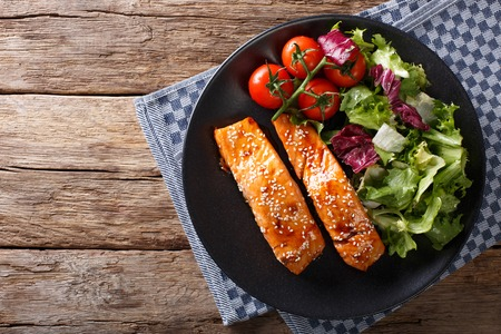 Salmon with sesame seeds in Asian style and fresh salad close-up on a plate. horizontal view from above Standard-Bild