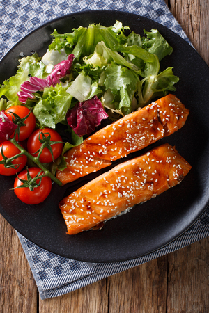 Baked salmon fillet with sesame seeds and fresh salad closeup on a plate. Vertical view from above Stock Photo