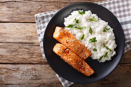 Glazed salmon fillet with rice garnish close-up on a plate. horizontal view from above