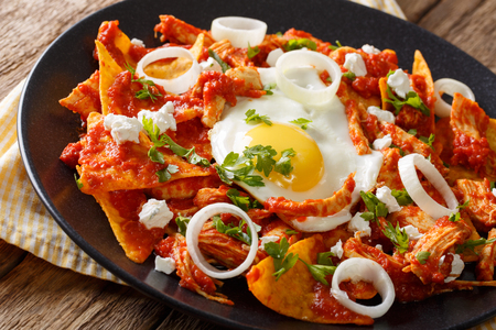 Mexican chilaquiles with fried egg and chicken close-up on a plate. horizontal