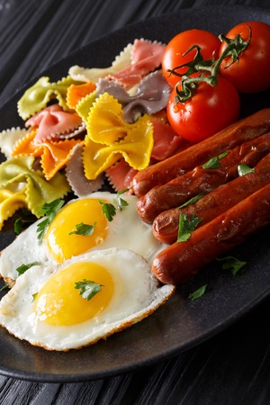 hearty breakfast: fried eggs, sausages, farfalle pasta and tomatoes close-up on a plate. vertical Stock Photo