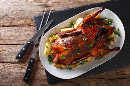 Schönes Essen: gebackene ganze Ente mit Äpfeln close-up auf einer Platte auf dem Tisch. Horizontale Ansicht von oben Standard-Bild