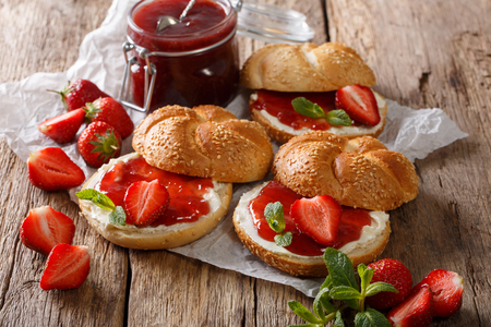 Breakfast sandwiches with strawberry jam, fresh berries, cream and mint closeup on the table. horizontal