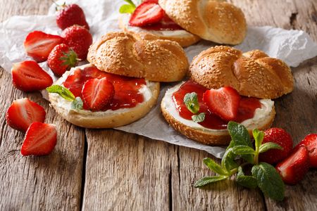 Breakfast bun with strawberry jam, fresh berries, cream and mint closeup on the table. horizontal