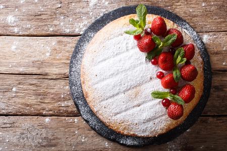 todo el pastel de sándwich Victoria, decorado con fresas, arándanos y menta closeup en la mesa. vista horizontal desde arriba