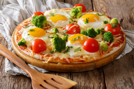 Pizza with eggs, cheese, broccoli, tomatoes and herbs close-up on the table. horizontal Stockfoto