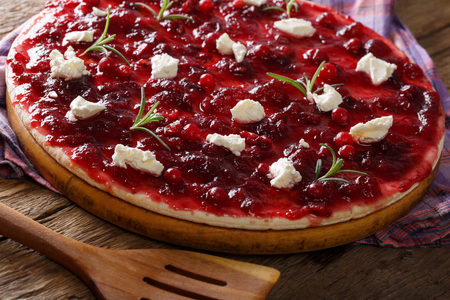 Freshly baked flatbread with cranberry sauce, goat cheese and rosemary close-up on a board. horizontal Фото со стока