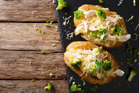 Hearty hot baked potato with broccoli, chicken, onion and cheese close-up on the table. horizontal view from above