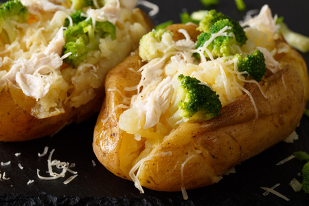Healthy baked potato with broccoli, chicken, onions and cheese close-up on the table. horizontal